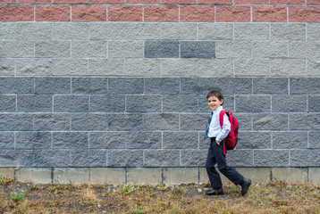 smiling young school boy with backpack walking to school
