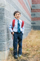 happy boy in school uniform laughs outside of a school building