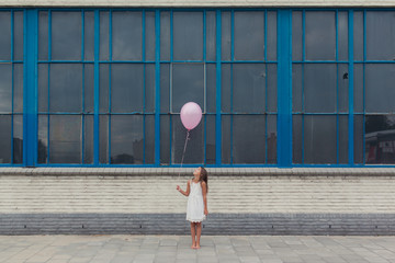 Little girl in white dress with pink balloon in front of old building