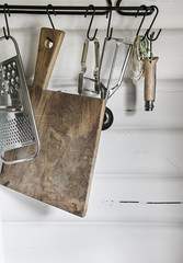 Kitchen utensils and chopping board hanging from rack in kitchen