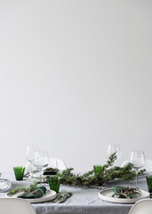 Dining table setting with white plates and green glasses