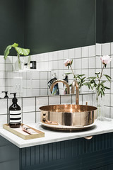 Interior of bathroom with white tiles and copper sink
