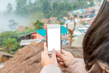 Hand holding cell phone to take a photo view of city on the mountain , blank screen on white