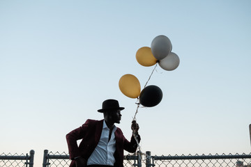 Young dapper male holding balloons