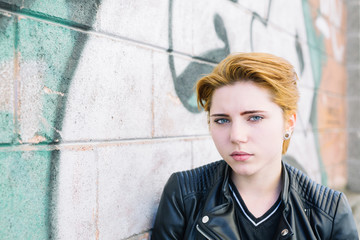 Young ginger teenager against a graffiti wall