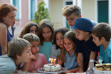 Group of children blowing the candles of a birthday cake