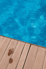 Wet Footprint on a Wooden Floor by the Pool