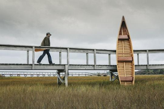 Man with wooden canoe in marsh, Marshfield, Massachusetts, USA