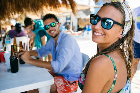 Young woman and man enjoying beers in a beach bar on a tropical location with their friends