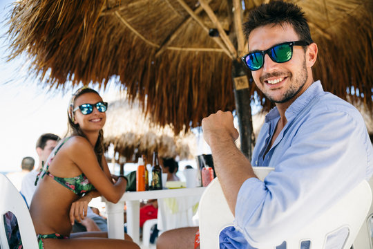 Happy young man and woman in a beach restaurant enjoying a meal with their friends