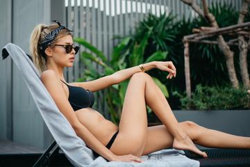 Attractive Blonde Woman Sunbathing in Black Bikini