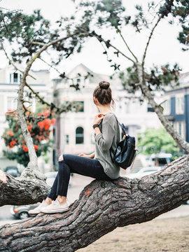 Woman sitting on tree in San Francisco