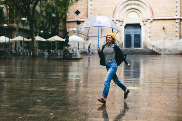 Woman running holding an umbrella on a rainy day.