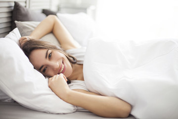 Happy morning. Portrait of a smiling pretty young brunette woman relaxing in white bed.