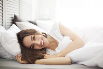 Healthy Happy Female Model Relaxing Indoors. Portrait of a smiling pretty young brunette woman relaxing in bed. Isolated.