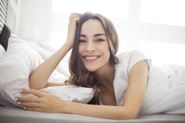Having Fun Lying On White Bed. Smiling Beautiful young woman in white bed in bedroom at home waking up.