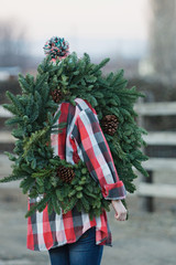 young woman carries evergreen wreath