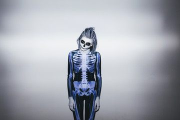 Young woman with skeleton costume and halloween make up against white wall