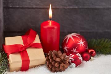 Geschenk und Kerze vor Holz zu Weihnachten
