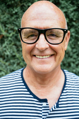 Stylish bald senior man portrait smiling, wearing glasses and a marine stripe tshirt looking at the camera.