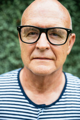 Stylish bald senior man portrait, wearing glasses and a marine stripe tshirt looking at the camera.