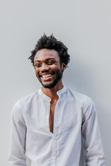 Afro American Man Smiling Over a White Wall