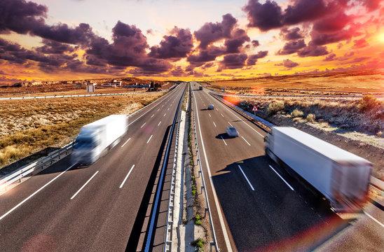 Camiones y autovia.Transporte internacional y logistica.Mercancia llegando a su destino por carretera. Industria del transporte