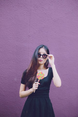 woman in sunglass posing with a candy