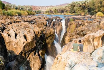 zwei Männer sitzen auf einem Felsen und schauen auf die Epupa Wasserfälle, Kunene, Namibia