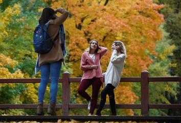 Women take photos on an autumn day in Neskuchny Garden in Moscow