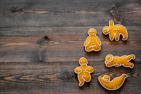 Gingerbread cookies in shape of yoga asanas on dark wooden background top view copyspace