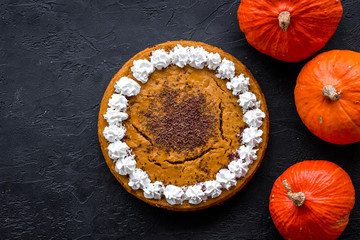 Homemade pumpkin pie decorated whipped cream and chocolate near pumpkins on black background top view copyspace