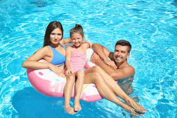 Young couple and cute daughter with inflatable ring in swimming pool