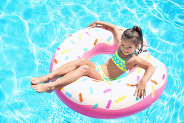Cute girl on inflatable ring in swimming pool