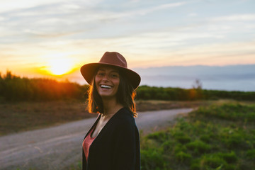 Woman smiling standing on the mountain at sunset.