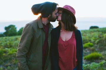 Young hipster couple in love kissing on the mountain.