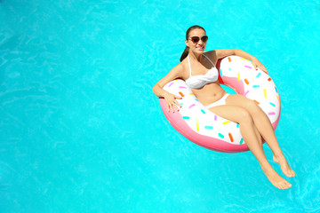 Young woman relaxing on inflatable donut in swimming pool