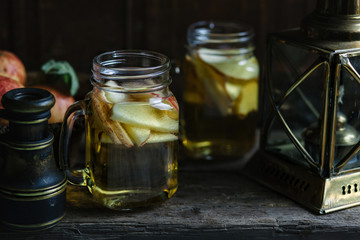 Jugs of apple cider in a rustic still life setting.