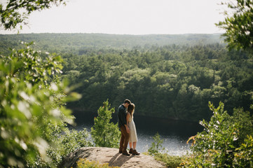 Fun adventurous intimate engaged couple on lookout over forest landscape