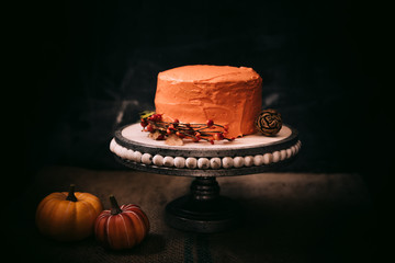 Autumn themed cake with orange icing on dark background.