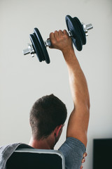 Back view of a man lifting weights sitting on a workout bench at home.
