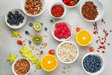Composition with nutritious oatmeal and different ingredients for breakfast on light background