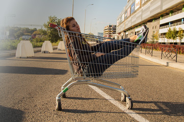 Beautiful girl sitting in a basket goes on shopping on the background of a shopping center