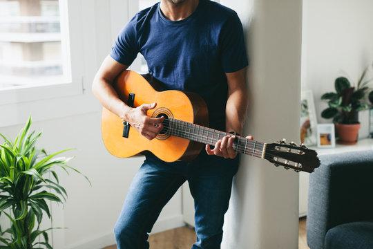 Closeup of a man playing guitar standing at home.