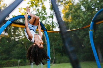 A young girl hanging upside down on a trampoline