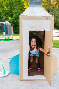 A young child with her cardboard box spaceship