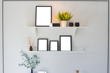 Blank black wooden frame and tree on shelf over white cement wall background, template