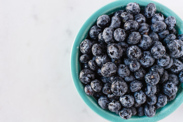 Top down view of blueberries in a blue bowl against a white background.