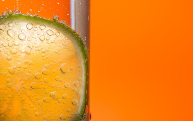 Slice of lime in sparkling water on orange background.