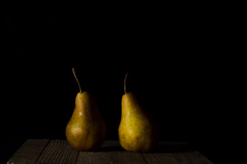 Two pears on dark background.